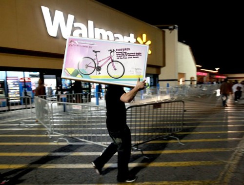 A shopper walks to his car after purchasing a bike at Walmart in Butler Plaza on Thursday, Nov. 24, 2011, in Gainesville, Fla. Walmart opened stores on Thursday. (AP Photo/Matt Stamey, The Gainesville Sun)