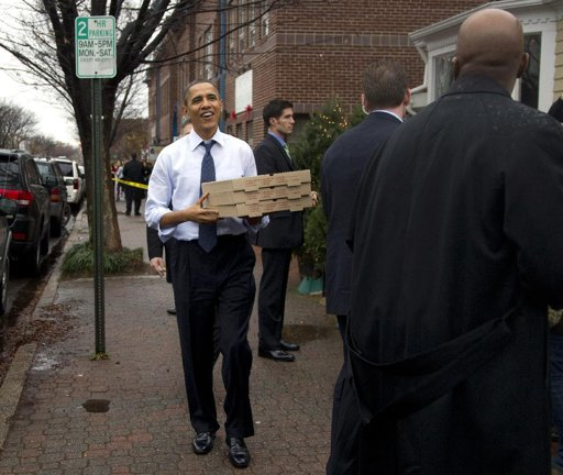President Barack Obama, arms full of pizza, walks out of Del Ray Pizzeria, after a visit, Wednesday, Dec. 21, 2011, in Alexandria, Va. (AP Photo/Carolyn Kaster)...