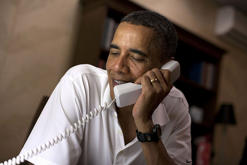 President Barack Obama makes phone calls to 10 American servicemembers stationed around the world from his vacation rental home in Kailua, Hawaii, Dec. 24, 2011. (Official White House Photo by Pete Souza)