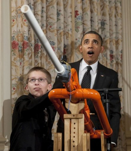 "US President Barack Obama reacts as 14-year-old Joey Hudy of Phoenix, Arizona, launches a marshmallow from Hudy's ""Extreme Marshmallow Cannon"" during a tour of the White House Science Fair in the State Dining Room of the White House in Washington, DC"