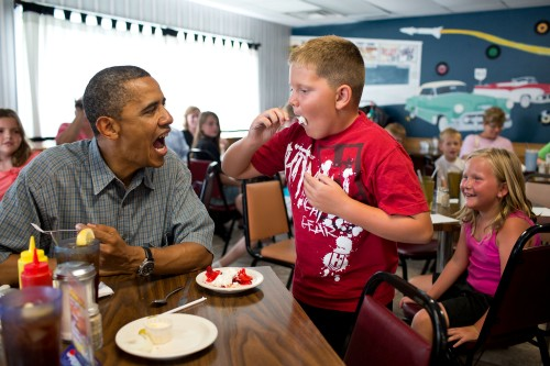 President Barack Obama shares his strawberry pie with a boy during a lunch stop at Kozy Corners restaurant in Oak Harbor, Ohio, July 5, 2012. (Official White House Photo by Pete Souza)