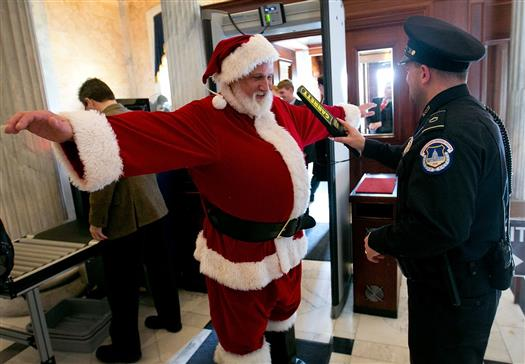 "Capitol Hill police check an unidentified man dressed as Santa Claus with a metal detector as he enters the U.S. Capitol on his way to Speaker of the House John Boehner's office on December 12, 2012 in Washington, DC. The man was working with the group Catholics United, and wanted to urge Speaker of the House John Boehner to pass pending ""fiscal cliff"" legislation before Christmas. (Photo by Win McNamee/Getty Images)"