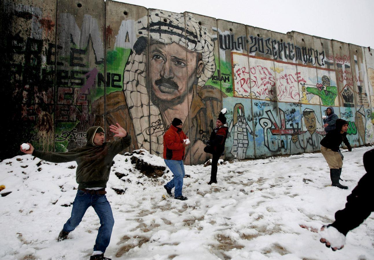 Palestinians play in the snow next to a section of Israel's separation barrier in Qalandia between Jerusalem and the West bank city of Ramallah, Thursday, Jan. 10, 2013. Stormy weather conditions continued on Thursday with snow, torrential rains and strong winds across the region. (AP Photo/Majdi Mohammed)