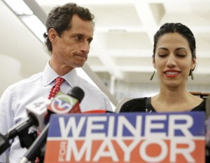 New York mayoral candidate Anthony Weiner glances at his wife, Huma Abedin, as she speaks during a news conference at the Gay Men's Health Crisis headquarters, Tuesday, July 23, 2013, in New York. The former congressman says he's not dropping out of the New York City mayoral race in light of newly revealed explicit online correspondence with a young woman. (AP Photo/Kathy Willens)