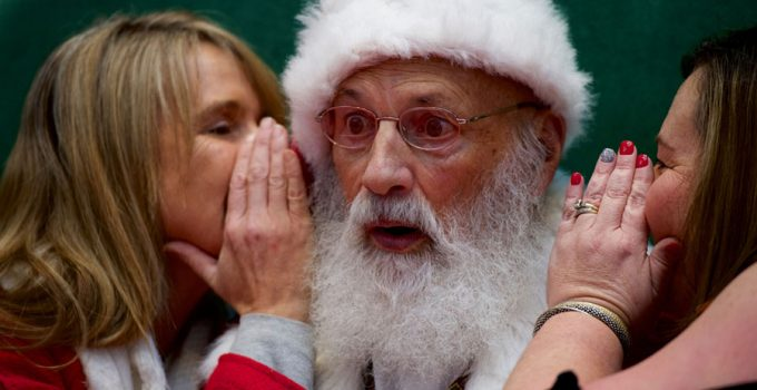 Santa Claus reacts as (L) Tami McEleney and (R) Patrice Conner whisper in his ear at the King of Prussia Mall, United States' largest retail shopping space, in King of Prussia, Pennsylvania, U.S., December 8, 2018. REUTERS/Mark Makela
